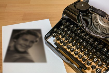 MANUAL TYPEWRITER NEXT TO SEPIA PHOTOGRAPH OF WOMAN